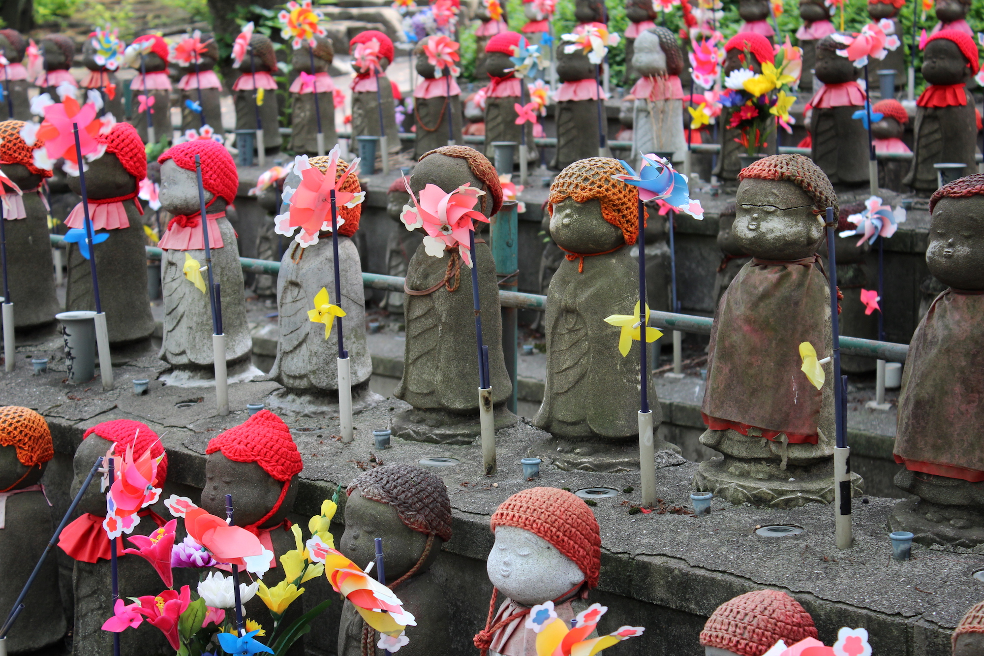 Rows of small statues with handmade bonnets